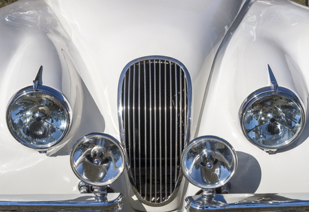 Close up of white vehicle hood and grill with chromed headlamps, spot lamps and bumpers