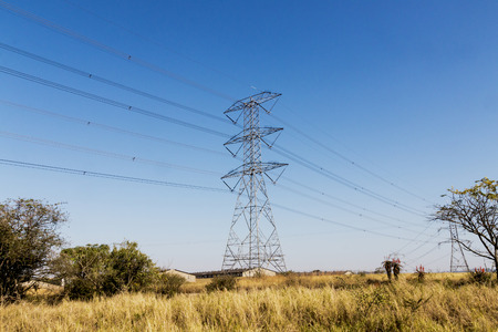 torres eléctricas: Overhead electric powerlines and pylons stretching across dry rural winter landscape in South Africa