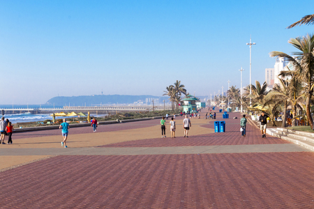 DURBAN, SOUTH AFRICA - JULY 7, 2017: Early morning view of many unknown pedestrians and cyclists on paved promenade on the Golden Mile beachfront in Durban, South Africa