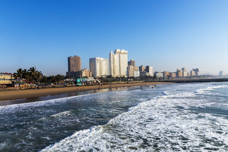 DURBAN, SOUTH AFRICA - JULY 7, 2017: Early morning view of waves breaking on beach against blue Durban city skyline in South Africa