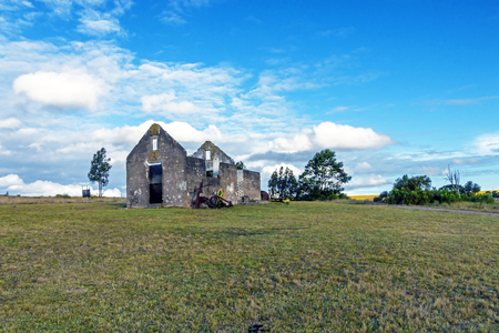 Rural old abandoned derelect farm building on dry winter landscape against blue cloudy sky in Lake Eland Game reserve in South Africa