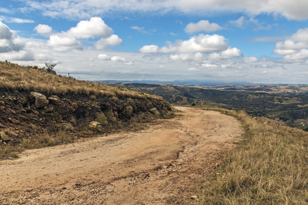 Gebogener ländlicher Schotterweg durch trockenes Gras gegen hii's Täler und blauer bewölkter Himmel gestalten am See Eland Game Reserve in KwaZulu-Natal in Südafrika landschaftlich Standard-Bild