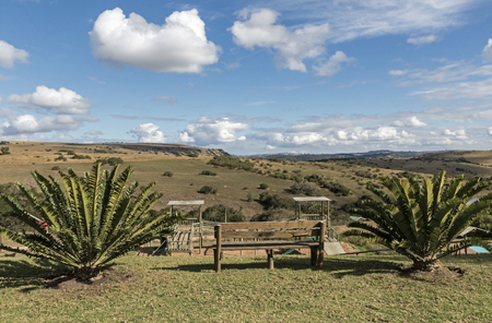 reserve: Wooden bench cycads and childrens jungle gym against winter hills valleys and blue cloudy sky landscape at Eland Game Reserve in KwaZulu-Natal in South Africa