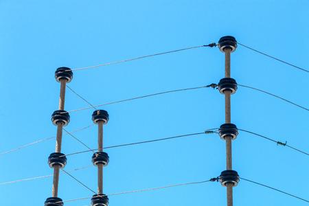 Ciérrese encima de instalación eléctrica montada en la pared de la cerca de seguridad eléctrica de alto voltaje aislada contra fondo del cielo azul Foto de archivo