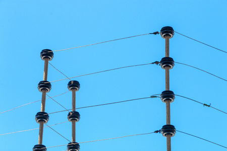 wired: Close up wall mounted high voltage electric security fence instalation isolated against blue sky background