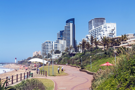 UMHLANGA, DURBAN, SOUTH AFRICA - OCTOBER 31, 2017: Many unknown visitors and promenade on beachfront against coastal commercial and residential city skyline in Umhlanga, Durban South Africa Editorial