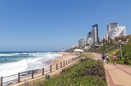 UMHLANGA, DURBAN, SOUTH AFRICA - OCTOBER 31, 2017: Many unknown visitors and promenade on beachfront against coastal commercial and residential city skyline in Umhlanga, Durban South Africa Banco de Imagens - 88953951