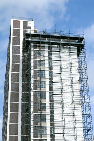 Underview of high skyscraper building with scaffolding undergoing renovations against blue cloudy sky in South Africa