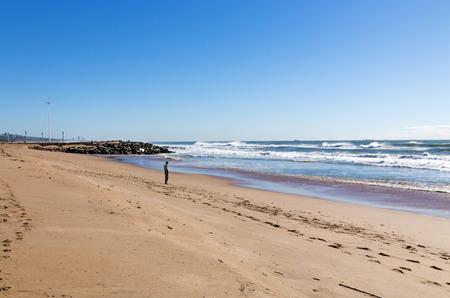 Single unrecocnizable man on Blue Lagoon Beach against ocean and blue coastal skyline landscape in Durban, South Africa Stock Photo