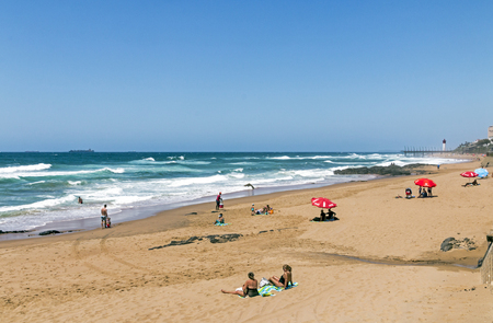 UMHLANGA, DURBAN, SOUTH AFRICA - AUGUST 31, 2017: Coastal landscape of many unknown people on early morning visit to uMhlanga beach in Durban, South Africa