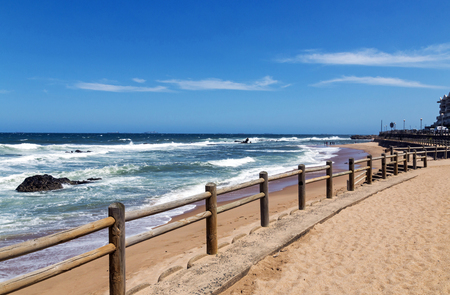 Wooden pole barrier on beachfront against beach sea ond blue sky landscape at Mdloti in Durban, South Africa