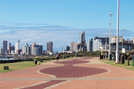 Quiet early morning paved promenade against city skyline and blue cloudy sky in Durban, South Africa