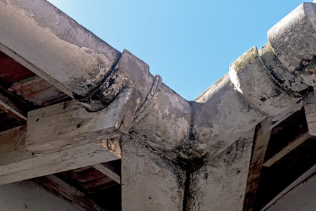 Close up of neglected vintage mouldy asbestos corner gutters and peeling wooden trusses on residential building Imagens