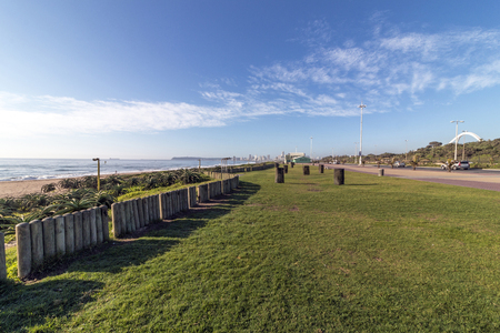 Empty grass verge lined paved promenade dune vegetation and sea against distant Durban city blue cloudy skyline coastal landscape in South Africa