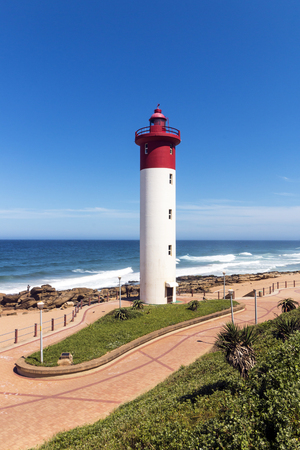 Red and white lighthouse on paved beachfront promenade against blue sky coastline at Umhlanga beach in Durban, South Africa