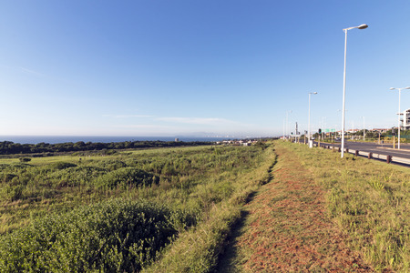 Scenic landscape view from Mhlanga Ridge overlooking green vegetation ocean and distant Durban City skyline and blue sky in South Africa