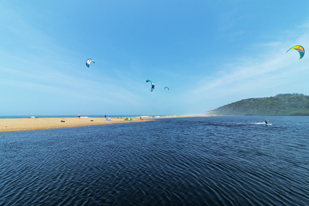 Kite surfers at Mhloti river mouth against blue skyline coastal landscape in Durban, South Africa   Imagens