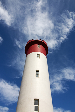 Upward close up view of red and white lighthouse and windows rising towards  blue cloudy sky at Umhlanga beach in Durban, South Africa
