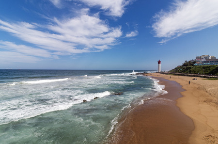 Waves breaking on beach, lighthouse city skyline and blue cloudy sky in Umhlanga,  Durban, South Africa