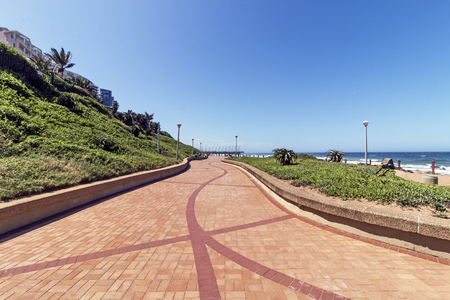 Green vegetation lined paved and patterned promenade coastal seascape and clear blue sky in Umhlanga, Durban, South Africa