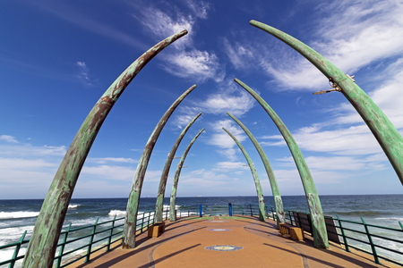 Close up view curves, paved pattern and texture on empty Whalebone pier against blue cloudy coastal skyline at Umhlanga, Durban, South Africa