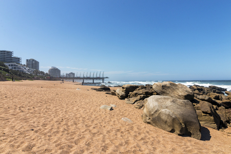 Beach sand rocks and ocean waves against blue coastal city skyline in Umhlanga, Durban, South Africa Banco de Imagens - 97306138