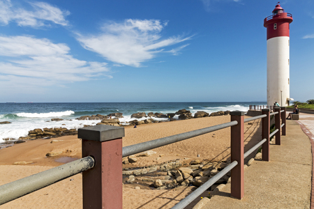 Walkway with metal barrier against red and white lighthouse against blue cloudy coastal seascape at Umhlanga, Durban, South Africa
