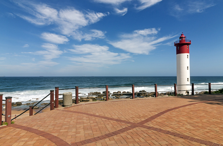 Paved and patterned walkway with metal barrier against red and white lighthouse against blue cloudy coastal seascape at Umhlanga, Durban, South Africa