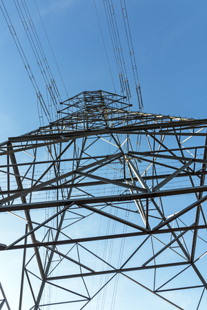 Portrait close up  underview of patterns and structured  metal engineering of overhead electricity pylon against blue sky background