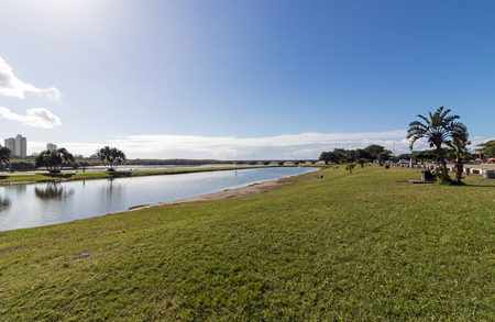 Morning view of green lawn against Blue Lagoon Estuary and blue cloudy coastal skyline in Durban South Africa