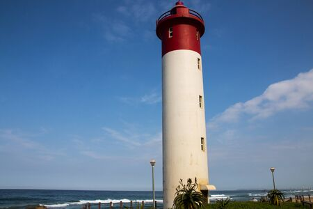 close up of the umhlanga lighthouse with the ocean and the sky in the background