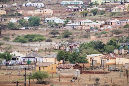 Housing and huts scattered informally on hill in rural south africa