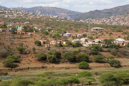 Wohnen und Hütten, die informell über Hügel im ländlichen Südafrika verstreut sind Standard-Bild