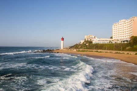 The lighthouse at umhlanga with waves breaking on the shortline