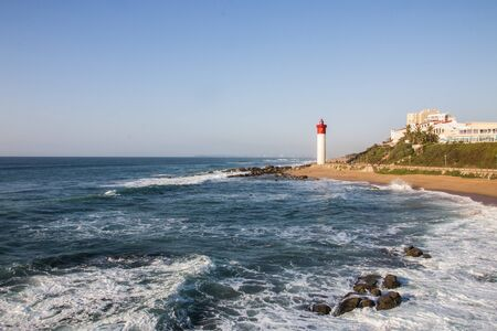 The lighthouse at umhlanga overlooked by buildings with waves breaking on the rocks