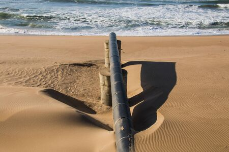 Exposed long black pipe leading into sea at low tide on coastline Imagens