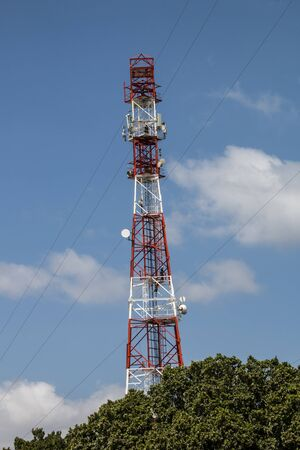 Towering red and white radio and television tower against blue sky
