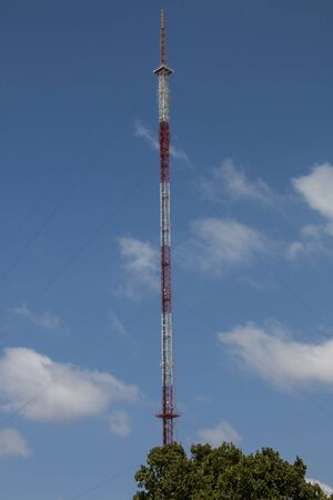 Extremely high red and white radio tower against cloudy blue sky