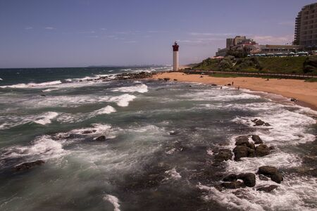 View of umhlanga lighthouse from shallows overlooking rocks and hotel