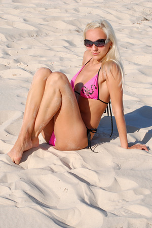 girl at the beach lying on the sand photo