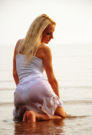 girl in clothes in the water in a wet dress posing Stock Photo