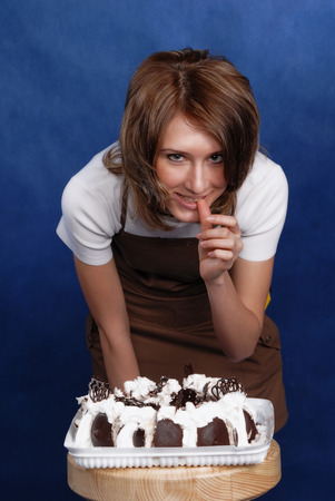 licking finger: girl and cake, holding sweets, closeup, studio Stock Photo