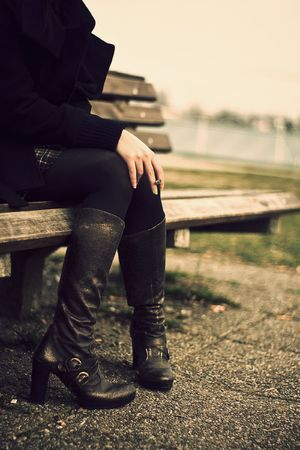 A girl waiting while sitting on a banch in high heel boots photo