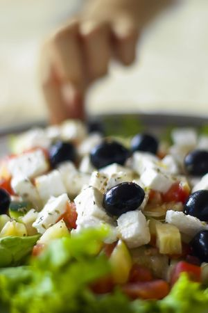 Greek salad in shallow depth of field with a hand in the background photo