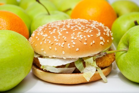 chicken burger next to many apples and oranges photo