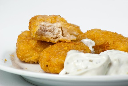 fried golden chicken nuggets on a plate with tartar sauce photo