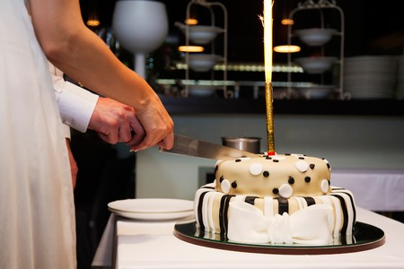 slicing: bride and groom cutting the cake Stock Photo