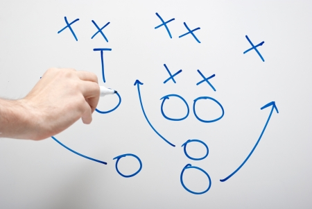 tactics: game plan on whiteboard with hand pointing Stock Photo