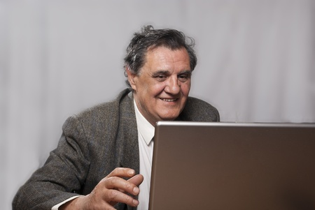 Portrait of a happy successful business man with a laptop on gray background Stock Photo - 9354015