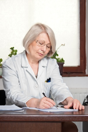 Female doctor in office with microscope writing  vertical photo